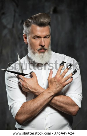 Portrait of stylish professional hairdresser with beard. Man wearing shirt, looking at camera and holding scissors of two kinds