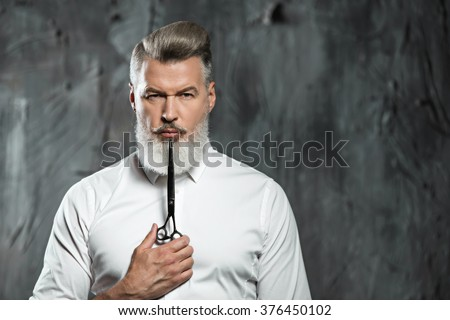 Portrait of stylish professional hairdresser with beard. Man wearing shirt, looking at camera and holding scissors near his beard