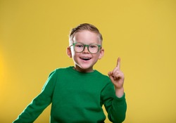 Portrait of stylish school boy with finger pointed up. Little child in glasses has idea. Kid isolated. Success, bright idea, innovation technology concept.