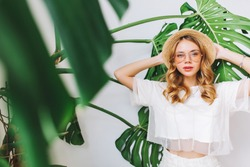 Portrait of stylish serious girl wears straw hat and trendy glasses posing beside exotic plant. Amazing blonde curly woman in white clothes standing on light background with big green leaves.