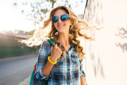 portrait of stylish smiling happy blond woman walking in street, curly hair, attractive, sunny, summer fashion trend, shirt, traveler, sunglasses, cheerful, backlight, positive mood,