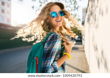 portrait of stylish smiling happy blond woman walking in street with backpack, curly hair, attractive, sunny, summer fashion trend, shirt, traveler, sunglasses, cheerful, backlight, positive, laughing