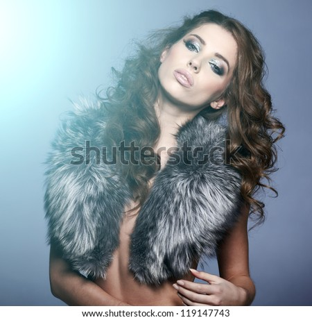 portrait of stylish woman in fur against grey background