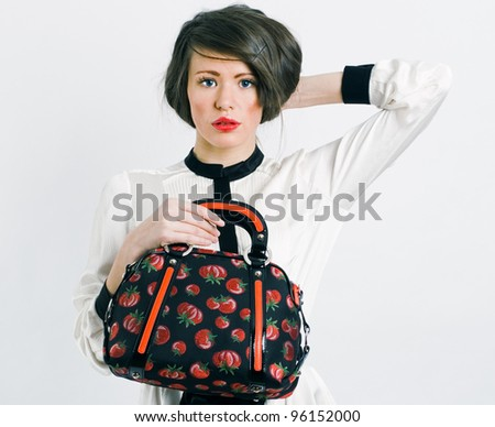 Portrait of stylish woman with a fashionable bag in his hand.