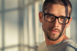 Portrait of stylish young man wearing eyeglasses at home. Closeup face of handsome guy with spectacles with sunlight and shadow reflection on face. Satisfied cool man looking at camera with copy space