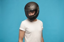 Portrait of stylish young man wearing white t-shirt and motorcycle helmet posing isolated at blue studio wall looking away. Motor sports, extreme lifestyle, transportation and people concept