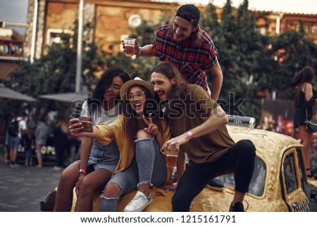 Portrait of stylish young people sitting on yellow car and taking picture with smartphone. Smiling bearded guys holding cups with cold beer while girl in hat showing victory sign