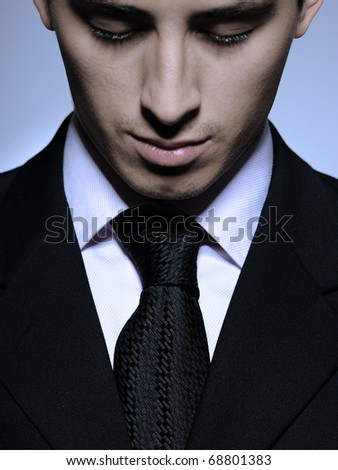 Portrait of succesful  business man in formal suit and black tie looking down. gray background