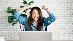 Portrait of success businesswoman enjoy success with laptop on work desk. Authentic shot joyful woman got jackpot, Surprised and celebrating her victory.