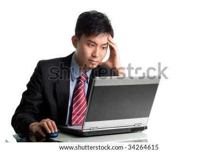 Portrait of successful Asian businessman at desk with laptop Mostly isolated in white with copyspace to right