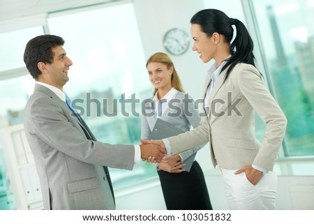Portrait of successful associates handshaking after striking deal
