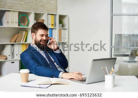 Portrait of successful bearded businessman speaking by phone and smiling while working at desk in light office