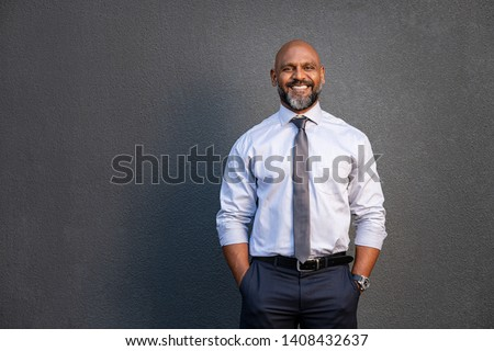 Portrait of successful black businessman standing against grey wall. Smilng senior entrepreneur in formal clothing looking at camera. Mature happy man isolated on grey background with copy space.