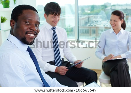 Portrait of successful boss looking at camera in working environment