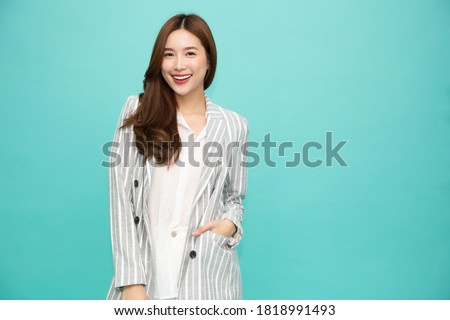 Portrait of successful business asian woman in suit and smile isolated over green background, Young businesswoman smiling and looking at camera, Happy feeling concept