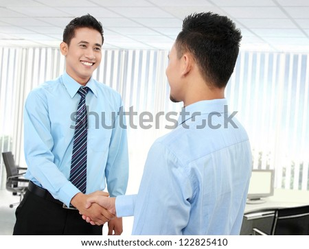 Portrait of successful business man shaking hands with eachother in the office