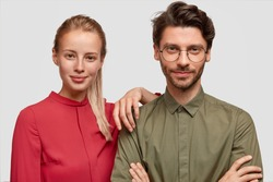 Portrait of successful business partners come on meeting, have confident expressions, being sure in their triumph. Beautiful charming woman leans at shoulder of best friend who stands hands crossed