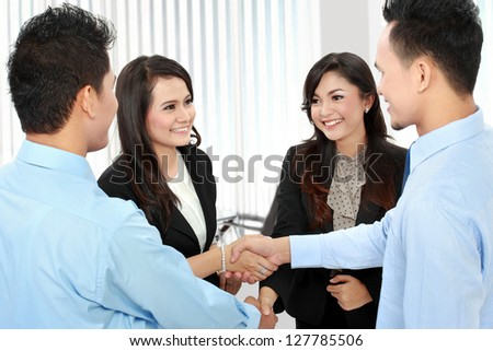 Portrait of successful business team shaking hands with each other in the office