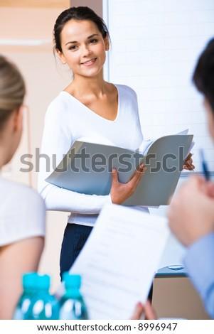 Portrait of successful business woman holding a folder and looking at her colleagues at meeting