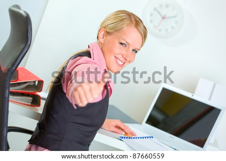 Portrait of successful business woman showing thumbs up