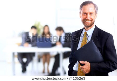 Portrait of successful businessman and business team at office