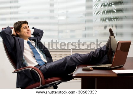 Portrait of successful businessman having rest on workplace in office