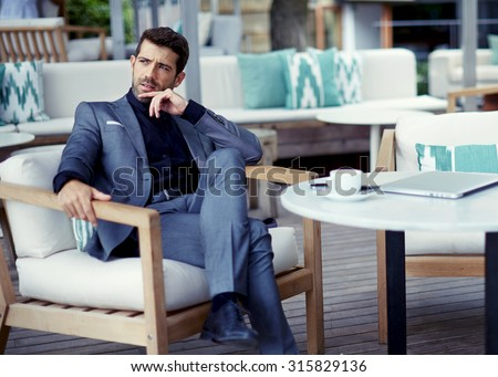 Portrait of successful businessman in a luxury expensive suit resting at cafe after hard work day and look pensive,rich entrepreneur waiting for a meeting with colleague at open air restaurant terrace