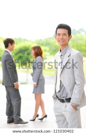 Portrait of successful businessman in suit looking at camera with his partners on background