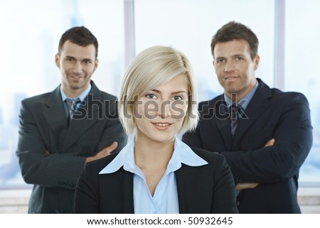 Portrait of successful businesspeople standing with arms folded in office.