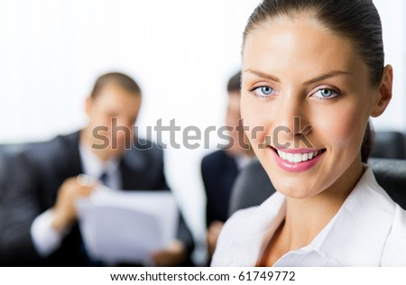 Portrait of successful businesswoman and colleagues on background, at office