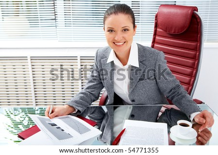 Portrait of successful businesswoman holding document while looking at camera with smile in office