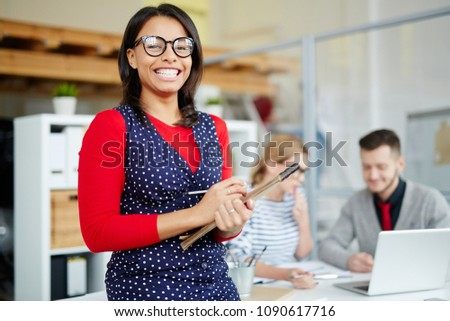 Portrait of successful businesswoman in eyeglasses standing at office with business people in the background #1090617716
