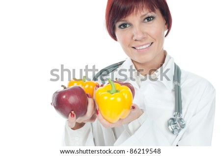 Portrait of successful cute young female doctor holding fresh fruits and vegs. Healthy-eating concept