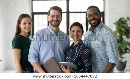 Portrait of successful diverse international business team friendly group of four coworkers capable reliable professional specialists posing at office standing close together smiling looking at camera Photo stock ©