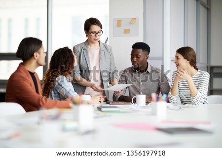 Portrait of successful female manager leading multi-ethnic team in meeting, copy space