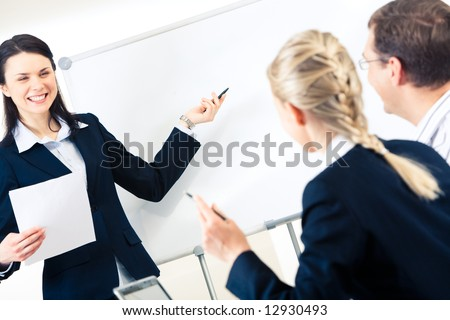 Portrait of successful girl explaining something on whiteboard to her colleagues