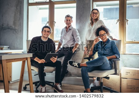 Portrait of successful group of people working at online web store. Men and women at ecommerce business office.