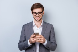 Portrait of successful handsome young man in formal wear with beaming smile, bristle and glasses holding smartphone and read sms while standing on gray background.