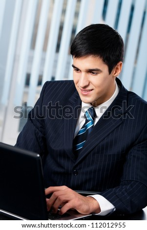Portrait of successful happy smiling business man working with laptop at office