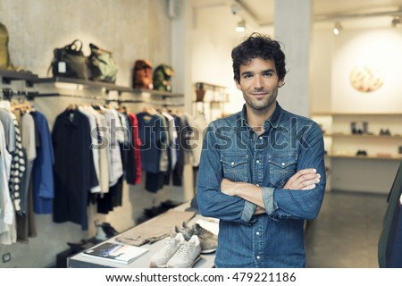 Portrait of successful male owner  with crossed arms in clothing store. Looking at camera