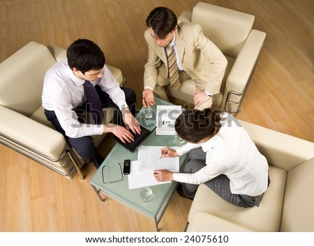 Portrait of successful people sitting on the armchair and discussing