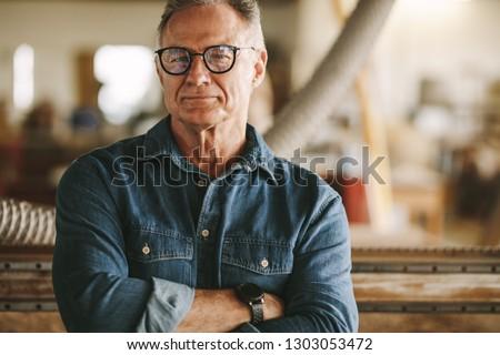 Portrait of successful senior man in eyeglasses standing in his carpentry workshop. Proud carpentry workshop owner standing with his arms crossed.