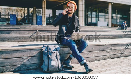Portrait of successful smiling hipster guy sitting on publicity area with laptop computer and making positive mobile conversation with friend, male looking at camera while communicate via cellular