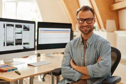 Portrait of successful software developer in eyeglasses standing with arms crossed and smiling at camera at office
