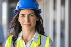 Portrait of successful woman constructor wearing helmet and safety yellow vest. Portrait of architect standing at building site and looking at camera with copy space. Mature successful woman engineer.