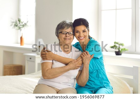 Portrait of supportive carer with her elderly patient who has Alzheimer. Happy retired senior woman together with caring young nurse or caregiver hugging and smiling sitting on bed in retirement home