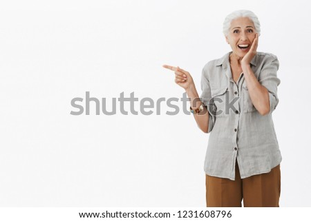 Portrait of surprised and delighted amazed cute granny in casual shirt touching cheek gently from excitement smiling joyfully from amazement pointing left with index finger over grey wall
