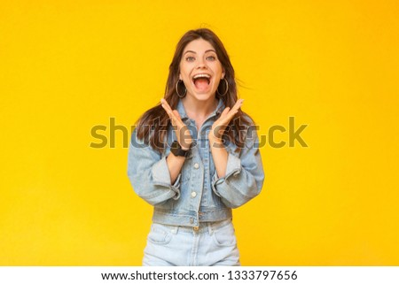 Portrait of surprised beautiful brunette young woman with makeup in denim casual style standing and looking at camera with open mouth and amazed face. indoor studio shot, isolated on yellow background