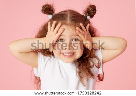 Portrait of surprised cute little toddler girl child over pink background. Looking at camera. Points hands to the left side. Advertising childrens products
