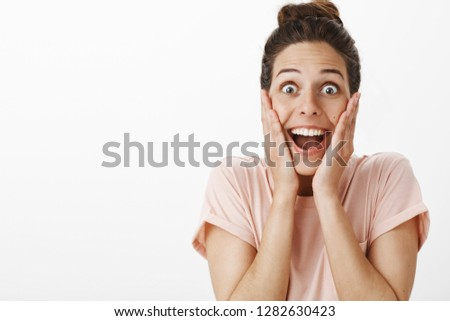 Portrait of surprised enthusiastic girl reacting to awesome unexpected surprise winning trip around world screaming from joy and amazement touching cheeks in amusement looking happy and joyful